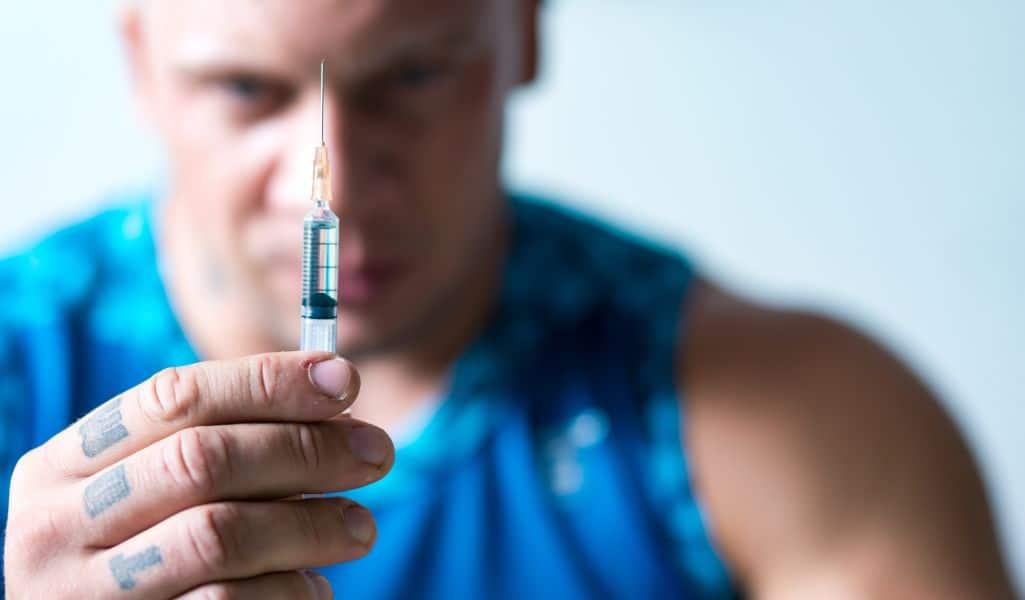 Bodybuilder holding steroid syringe